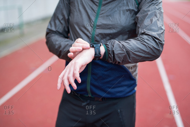Person using watch while standing on running track