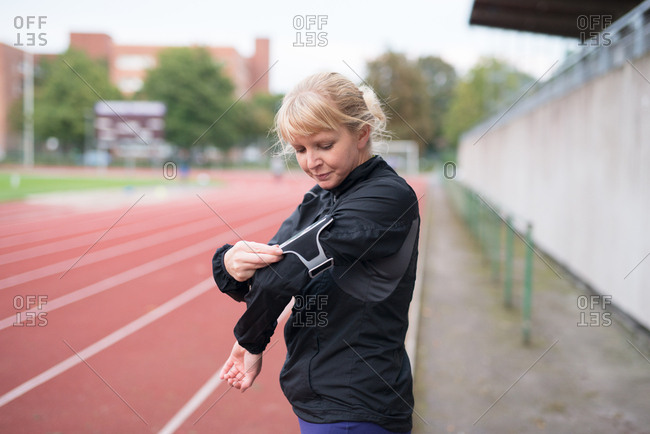 Woman using smartphone in armband while standing next to running track