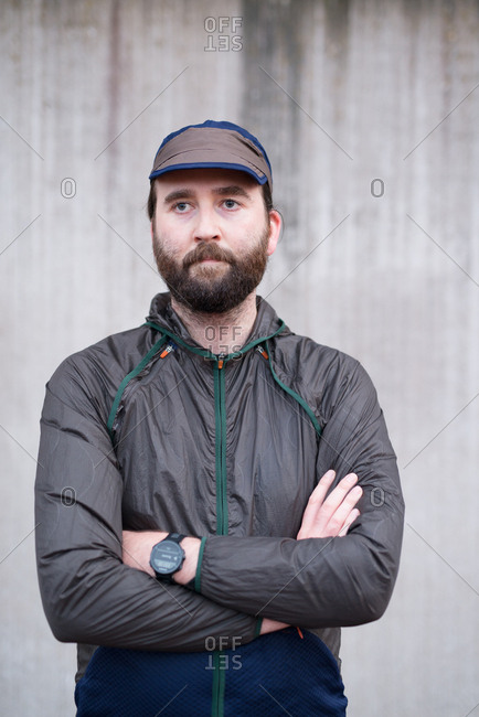 Bearded man with arms crossed wearing windbreaker, hat, and watch