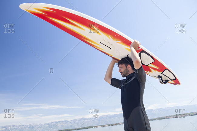 Surfer holding surfboard over head