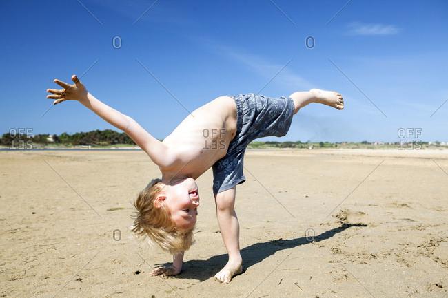 Blond boy on beach fooling around