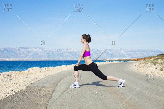 Young woman stretching leg on waterfront path