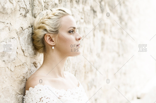 Portrait of bride leaning against wall