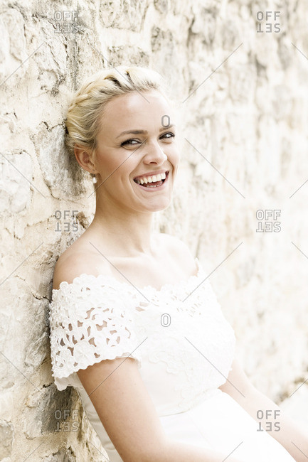 Portrait of laughing bride in white wedding dress