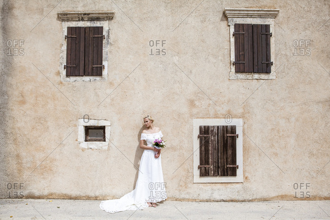 Bride in wedding dress standing in front of old house