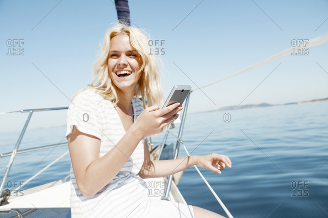 Young woman using smart phone on sailboat, Adriatic Sea