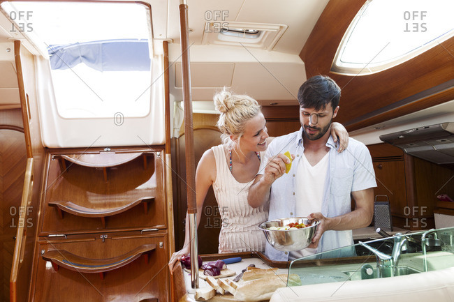 Young couple cooking together in galley of yacht, Adriatic Sea