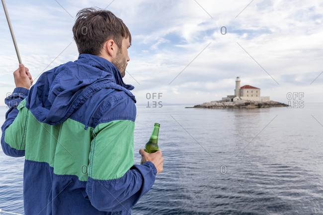 Man holding beer on sailboat, Adriatic Sea