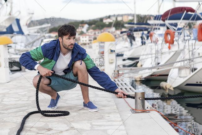 Man fixing rope on pier, Adriatic Sea