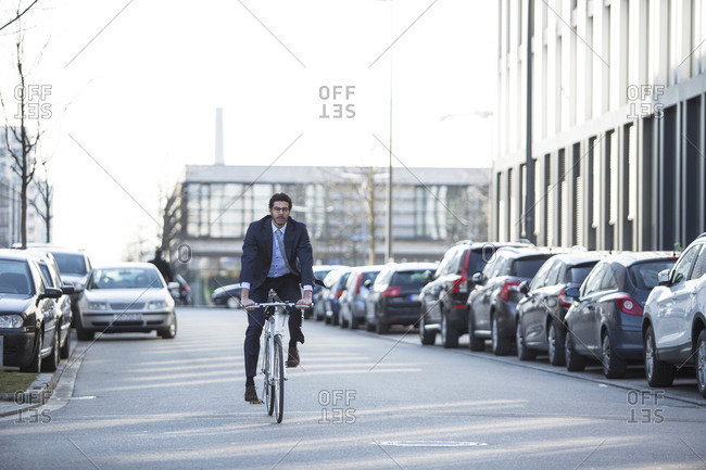 Businessman riding bike in city street