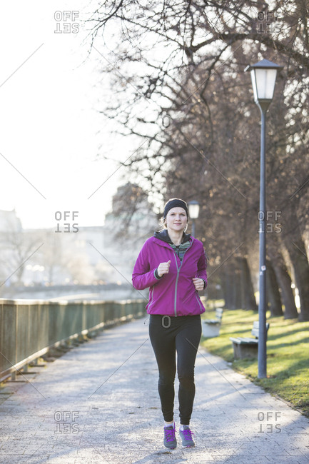 Woman in sports clothes jogging on footpath in city