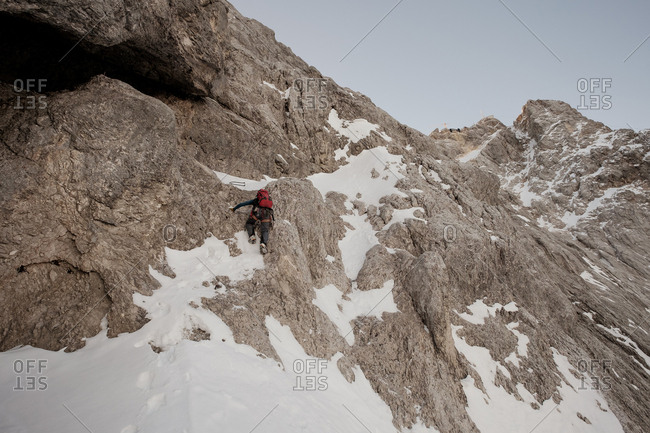 Lone mountaineer moving up snowcapped wall in mountain range