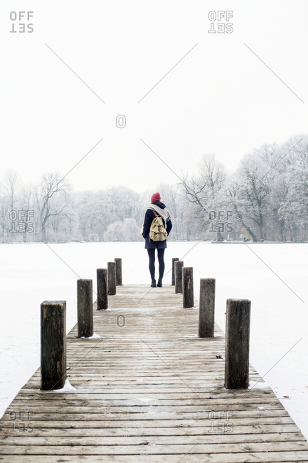 Mid adult woman on jetty looking at view in winter