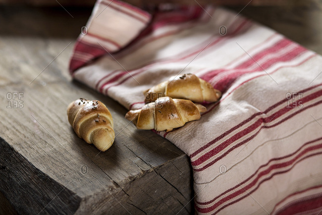 Fresh croissants placed on dish towel on wooden table
