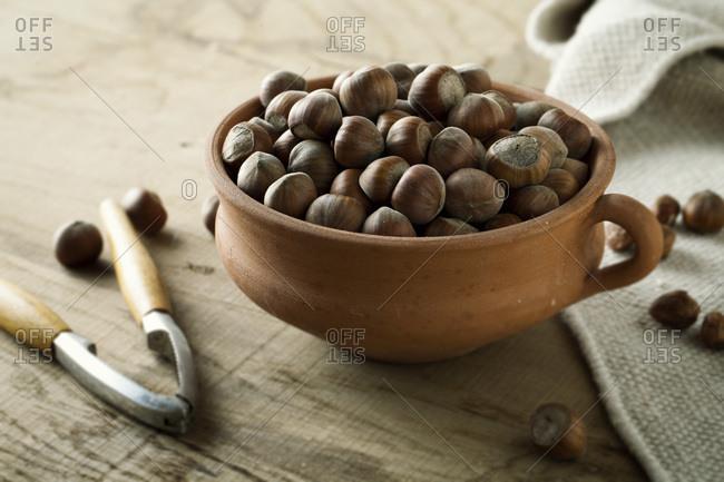 Nutcracker next to bowl with hazelnuts