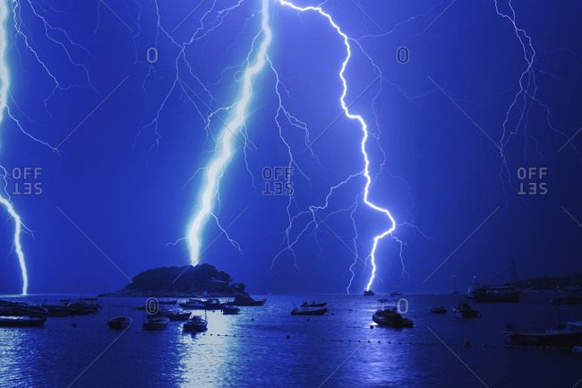 Lightnings in thunderstorm over harbor at night