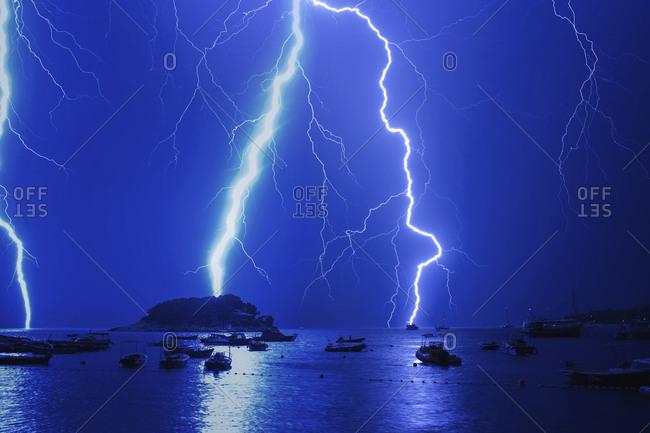 Lightnings in thunderstorm over harbor at night