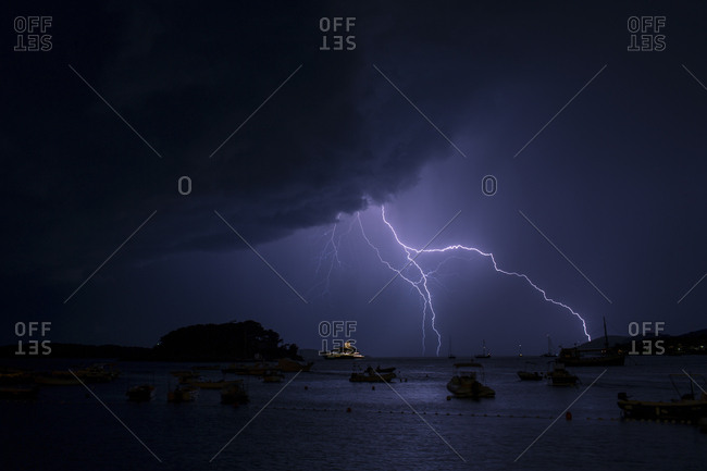 Lightnings in thunderstorm over sea at night