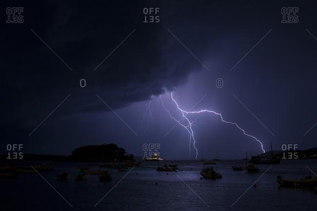 Lightnings in thunderstorm over sea at night