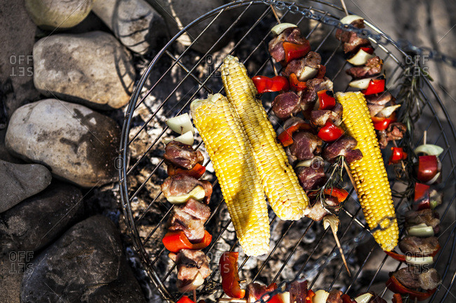 Barbecue on the riverside, meat skewers and corn on the cob, Bavaria, Germany