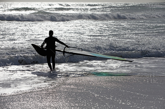 Silhouette of male windsurfer carrying windsurfing board in sunny ocean onto beach