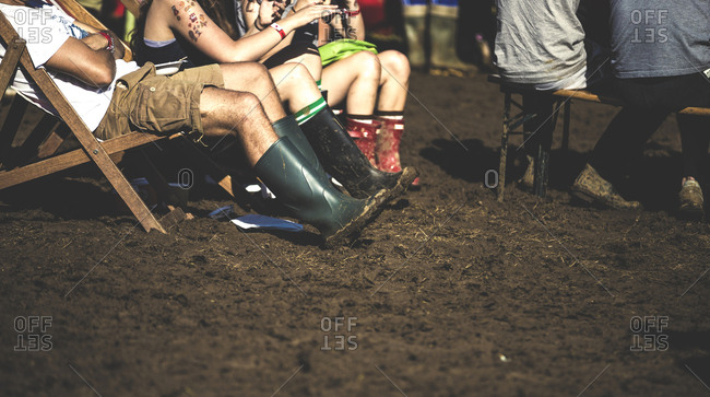 People sitting on chairs in mud wearing rubber boots