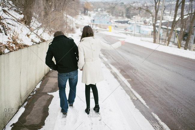 Couple walking together on a slippery snow covered sidewalk