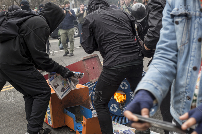 Washington, DC - JANUARY 20, 2017:  Protesters start a fire with newspaper boxes and a city recycling bin during Donald Trump Inauguration Day Protests