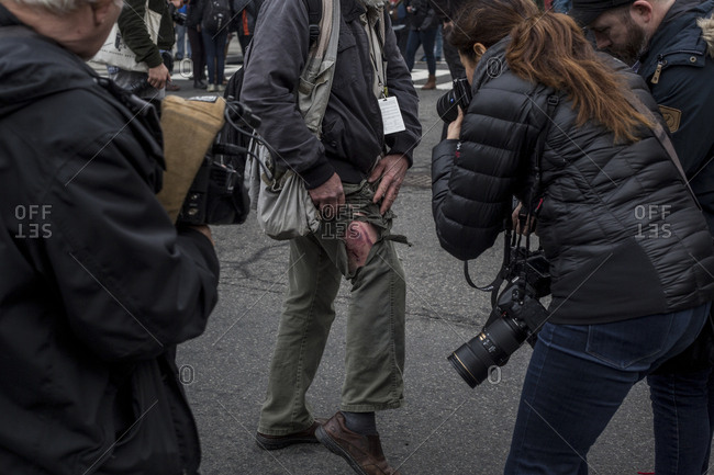 Washington, DC - JANUARY 20, 2017: A Photographer is photographed by other photographers while showing where his clothing was ripped and his leg injured during Donald Trump Inauguration Day Protests
