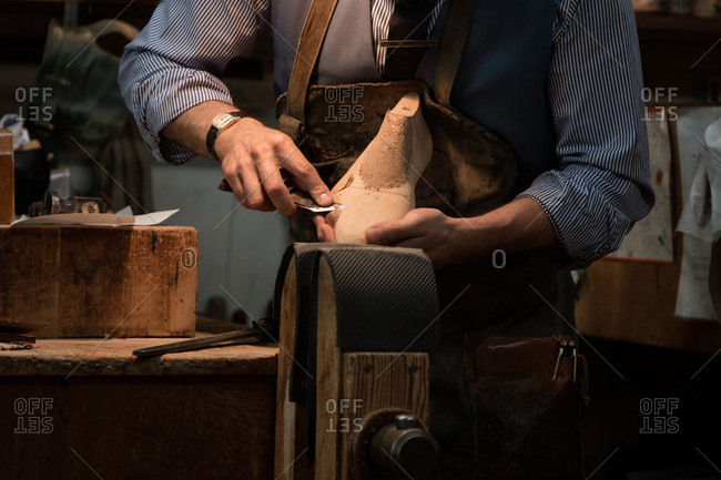 A cobbler crafting in a workshop