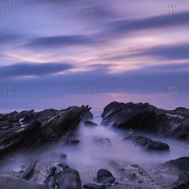Long exposure of the sunset sky over sea rocks in Jogashima, Miura Peninsula, Japan