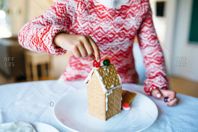 Girl decorating top of gingerbread house