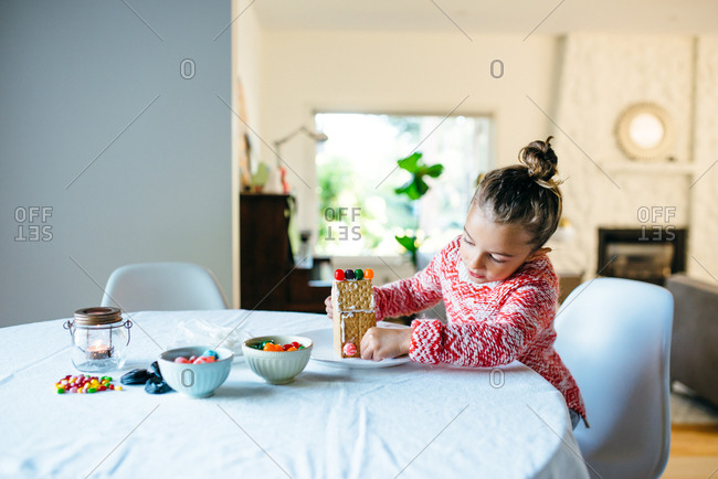 Girl putting together a gingerbread house