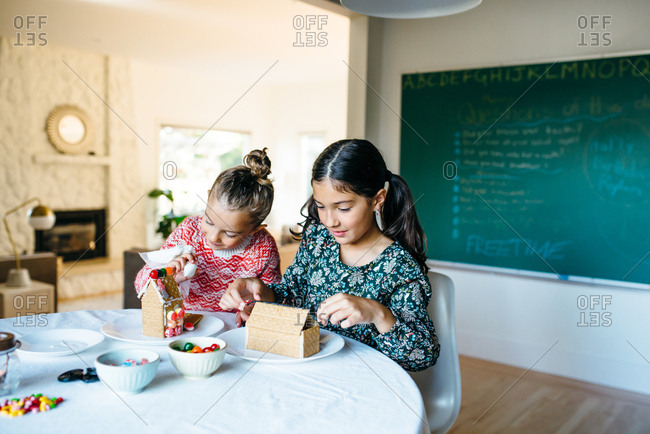 Girls making gingerbread house together