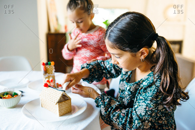 Girls decorating gingerbread houses together