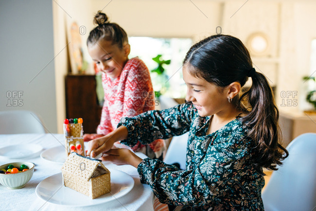 Girls icing gingerbread houses together