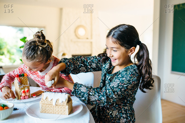 Girls having fun with gingerbread houses