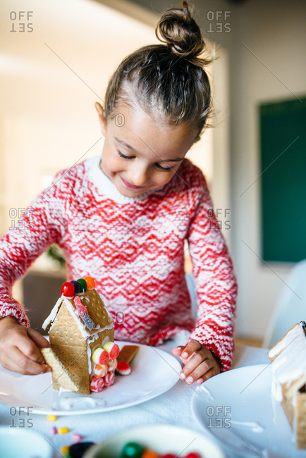 A girl making a gingerbread house