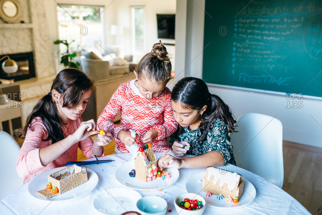 Three girls making gingerbread houses