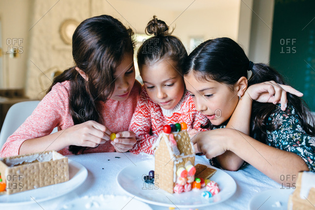 Three girls building gingerbread houses