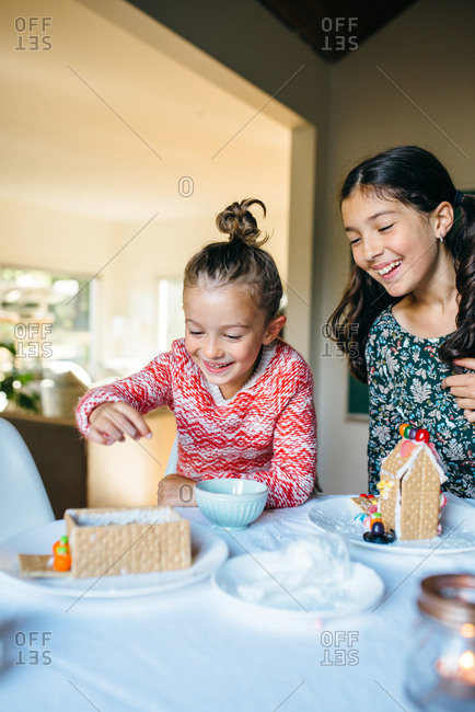 Girls smiling building gingerbread houses