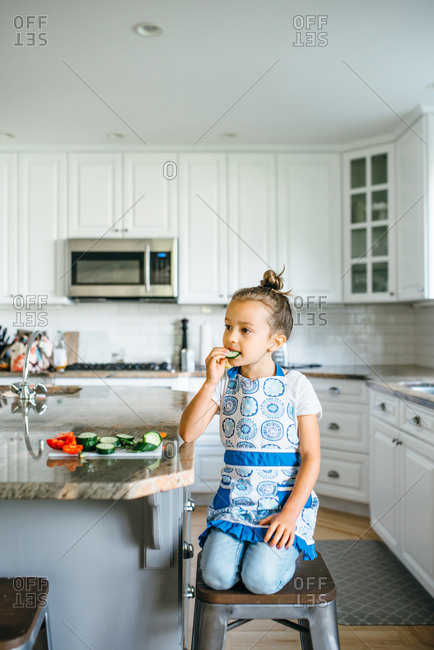 Girl in kitchen eating cucumbers