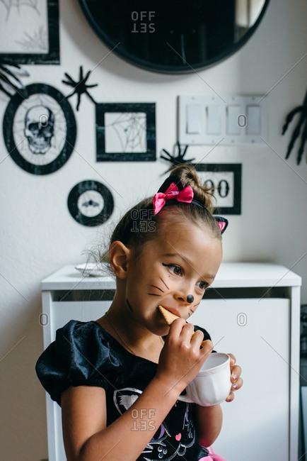 Girl having snack in Halloween setting