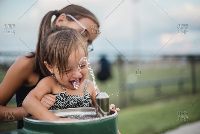 Girl helping sister at water fountain