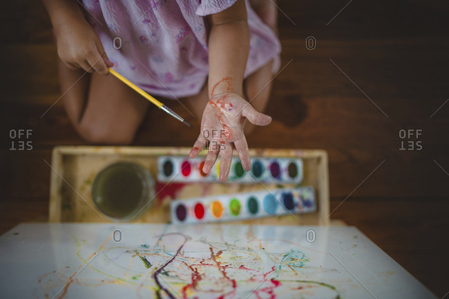 Girl with messy hands while painting