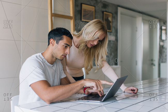 Couple checking computer together