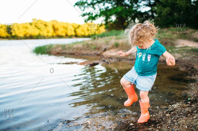 Toddler girl stomping in water on lakeshore