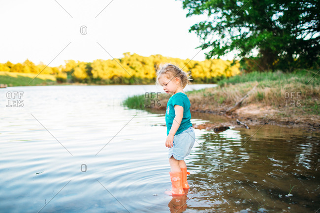 Toddler girl walking in lake with rubber boots