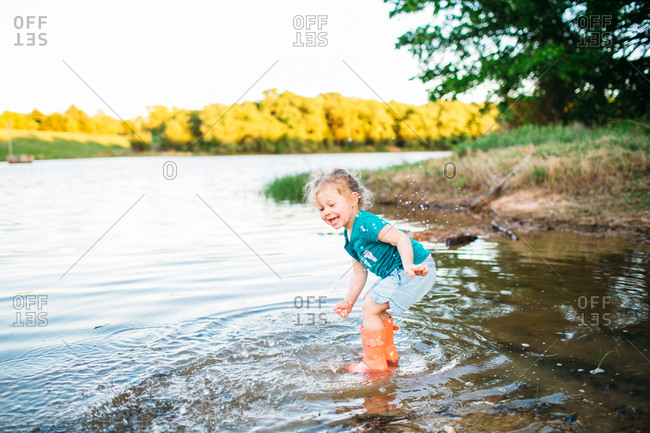 Toddler girl jumping in lake with rubber boots