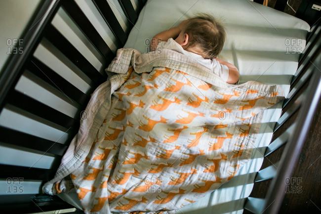 High angle view of baby sleeping in crib
